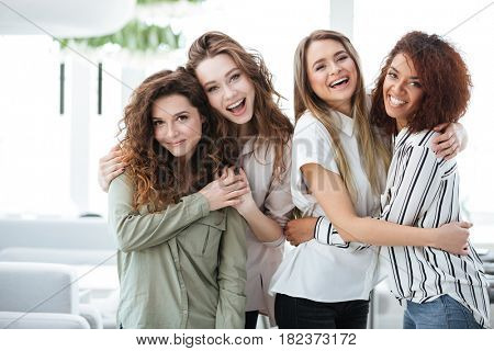 Four happy women posing in cafe and looking at the camera