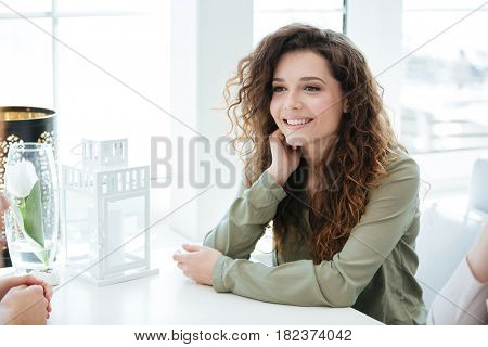 Side view of a happy woman sitting by the table and talking with friend in cafe