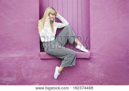 Young woman on the phone sitting on pink wall