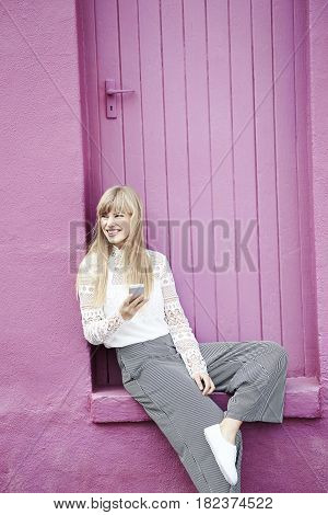 Happy young woman with cell phone sitting by pink doorway
