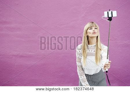 Blond beautiful woman kissing for selfie against pink