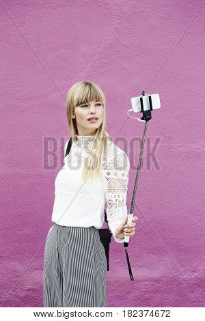 Blond and beautiful woman posing for selfie against pink