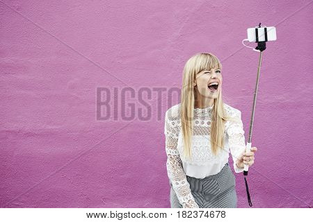 Winking young woman holding selfie stick against pink