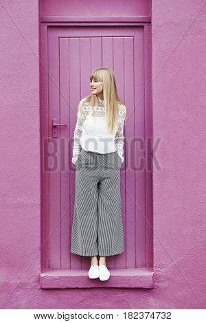 Stunning young woman standing in pink doorway