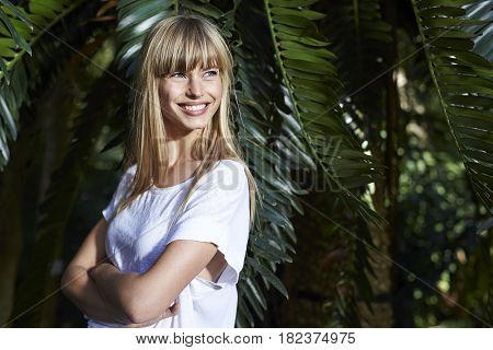 Smiling young blond beauty with arms folded
