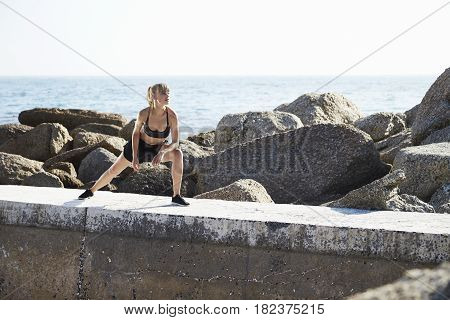 Lithe young model stretching on rocks at beach