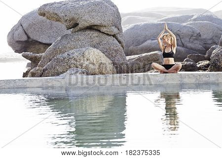 Young blond woman performing yoga pose by pond