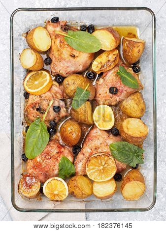 Top view of chicken thighs with potatoes, lemon and black olives, cooked in oven on gray concrete background. Baked chicken leg quarter in heat-proof glass. Vertical.