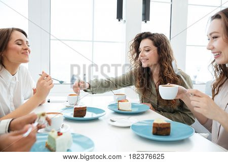 Cropped image of a four friends sitting by the table in cafe and eating cakes