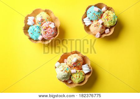 Wafer bowls with different ice-cream and marshmallows on color background