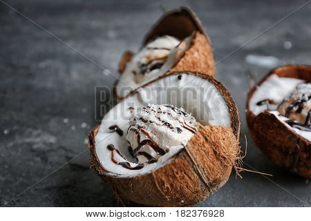 Ice cream with desiccated coconut and chocolate syrup in halves of nut on grunge background