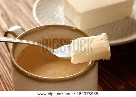 Cup of tasty butter coffee and shovel on wooden table, closeup