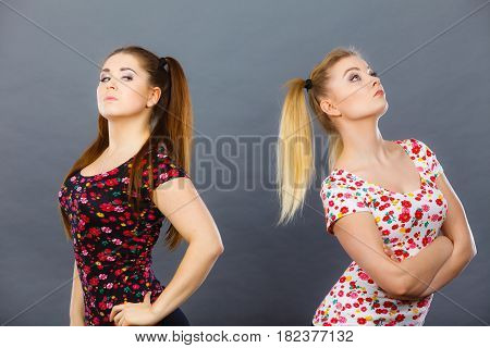 Two young women being offended by each other got the hump and standing backwards