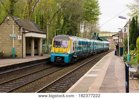 Chirk Wales UK - April 18 2017: The rural rail station at Chirk on the main line from Chester to Shrewsbury with an Arriva Trains passenger train the company provides rail and bus services in Wales and England
