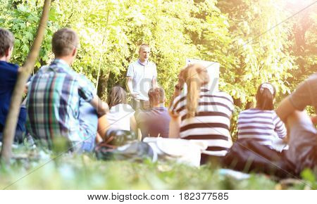 A group of young students in the park. View of a man gesticulating with his hands, standing against a defocused group of people sitting in front of him on the grass.