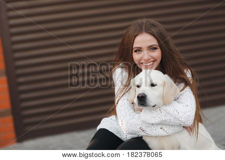 A young,beautiful woman with long,straight blond hair,a beautiful smile and white straight teeth,dressed in leggings black and white sweater posing outdoors in the spring,sitting in the city with his friend,an adult dog breed Golden Retriever