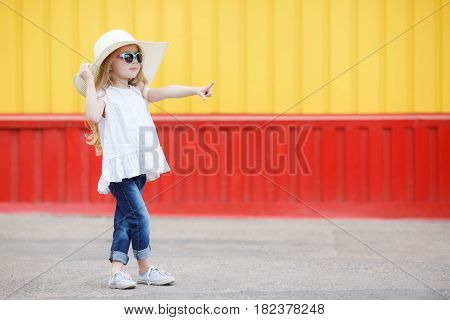 Beautiful little girl 6-8 years old,in a large straw hat from the sun,dressed in a short white dress without sleeves and blue jeans,with long blonde wavy hair and wears dark sun glasses in blue frame,posing standing near the school