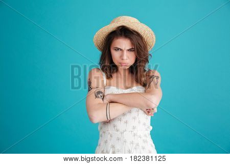 Portrait of grumpy moody girl in straw hat standing with arms folded and looking at camera isolated over blue background