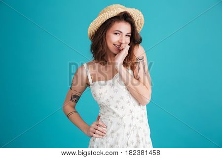Porrtrait of a smiling playful shy woman wearing summer clothes isolated over blue background