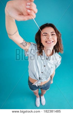Portrait of a young funny teen girl stretching and playing with buble gum isolated over blue background