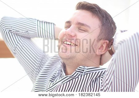 Portrait of a mature business man while relaxing with hands behind head