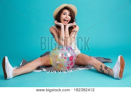 Portrait of a happy excited summer girl sitting on a blanket and leaning on a beachball isolated over blue background