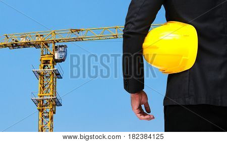 businessman hold in hand yellow safety helmet business industrial concept on yellow construction tower crane with blue sky background.