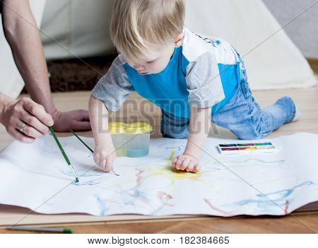Adorable small boy tries to paint with watercolors at home