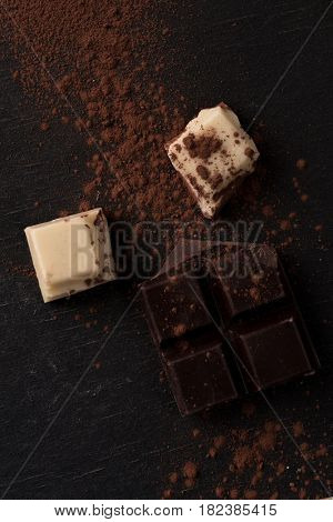 Top view of white and dark crashed chocolate bar tiles with powder over wooden background