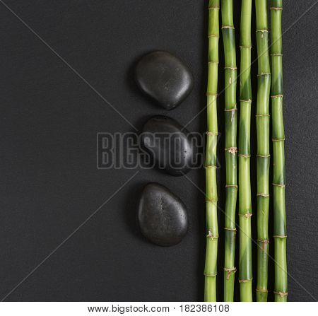 Spa concept with black basalt massage stones and a few stems of Lucky bamboo on a black background; with space for text