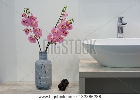White top ceramic washbasin glossy metal mixer and a bunch of artificial flowers on the left