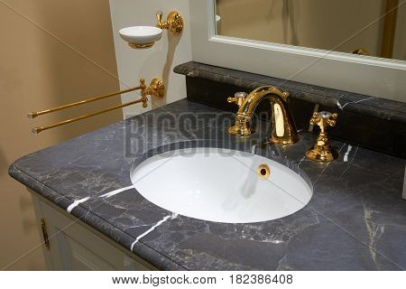 White inset ceramic washbasin in stone table and gold plated glossy metal mixer with crystals