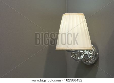 Old style switched on lamp mounted on wall with lampshade