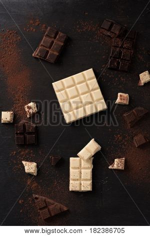 Top view of white and dark crashed chocolate bar tiles spread all over wooden background