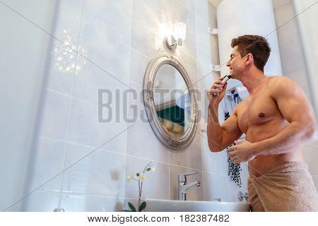 Handsome man shaving in bathroom reflection in mirror