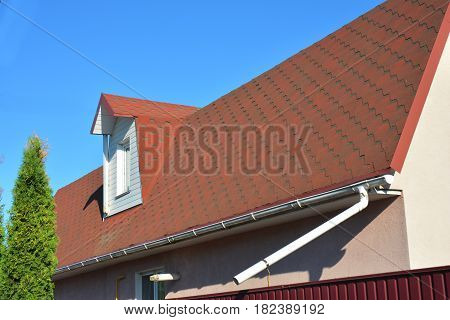 Old Roof Asphalt Shingles with Moss. Rain Gutter Pipeline with Downspout Pipe and Attic Mansard Window. Roofing Construction Roofing Repair.