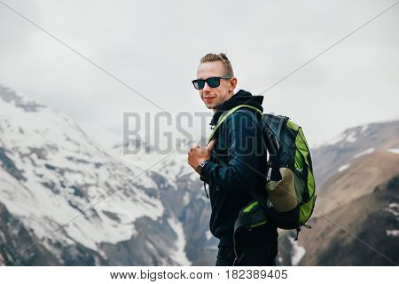 Young man with backpack standing on top of a mountain