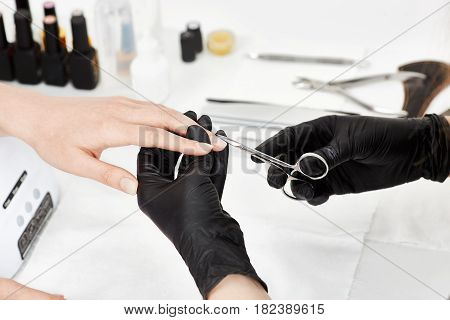 Nail care. Closeup of nail artist in black gloves cutting cuticle with manicure scissors. at salon.