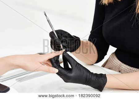 Closeup of professional nail artist making manicure removing cuticle with seel cuticle remover at salon.