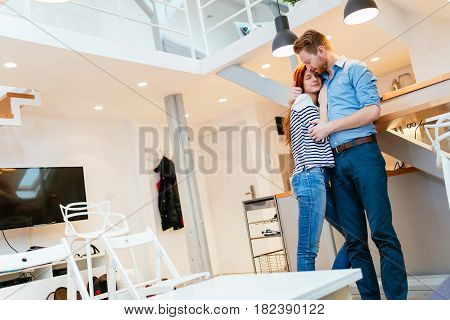 Man loving wife at home and hugging her with affection