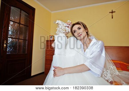 Bride On Silk Robe Looking On Her Wedding Dress Siiting On Bed At Room On Morning Day.