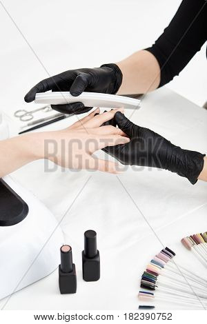 Professional nail technician in black gloves shortening nails before applying nail polish. Professional manicure set.