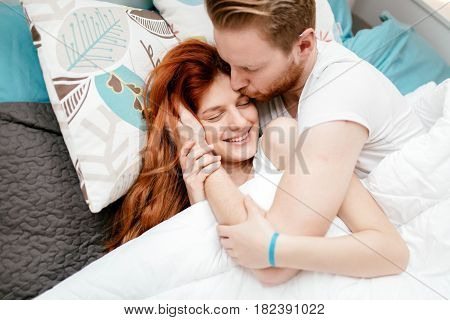 Beautiful couple in love awake in bed and smiling