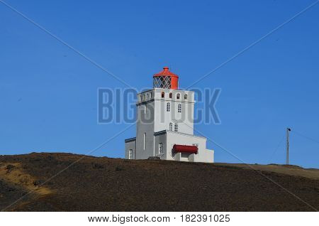 Red lantern on a white tower in Vik Iceland.