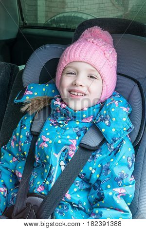 Little girl in jacket hat sitting in a baby car chair smiling. Car seat gray. Hat pink. The jacket is blue green with a pattern. The girl is wearing a seat belt.