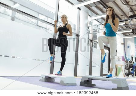 Beautiful women exercising aerobics in nice fitness club
