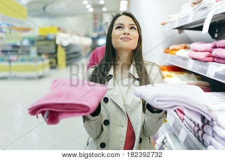 Beautiful woman inspecting and buying towels in supermarket