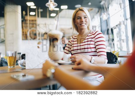 Beautiful women drinking coffee and gossiping in nice restaurant