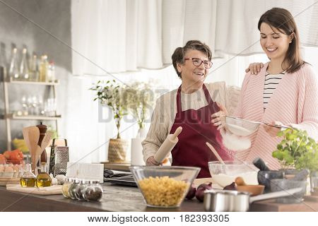 Grandma And Granddaughter Baking A Cake
