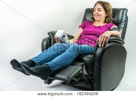 Pretty middle-age woman resting in black leather recliner armchair. Checking blood pressure using portable blood pressure machine.